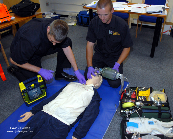 Paramedics demonstrate CPR on a dummy image